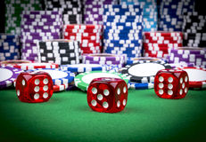 Pila de fichas de póker en una tabla verde del póker del juego con los dados del póker en el casino Jugar a un juego con los dado Fotografía de archivo