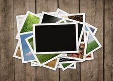 Pila de fotografías en el fondo de madera Fotografía de archivo libre de regalías