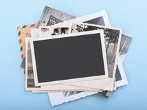Pila de fotos viejas en fondo azul Imágenes de archivo libres de regalías