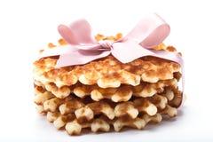 Pila de galletas redondas en el fondo blanco con la cinta rosada Imagen de archivo