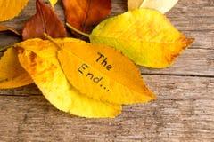 Pila de hojas de otoño caidas con la inscripción EL EXTREMO en el fondo de madera Imagen de archivo