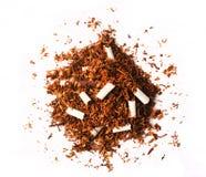 Pila de hojas del tabaco con los cigarrillos quebrados Fotografía de archivo libre de regalías