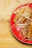 Pila de huesos y de esqueleto de pescados en la placa roja Imagen de archivo libre de regalías