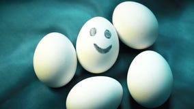 Pila de huevos, una sonrisa, diferente, colocando hacia fuera de anónimo a la muchedumbre, individualidad, energía positiva almacen de metraje de vídeo