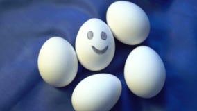 Pila de huevos, una sonrisa, diferente, colocando hacia fuera de anónimo a la muchedumbre, individualidad, energía positiva metrajes