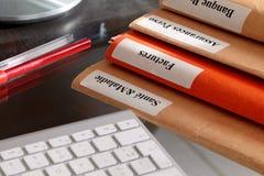 Pila de la carpeta en una mesa con el teclado Fotografía de archivo libre de regalías