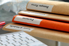 Pila de la carpeta en una mesa con el teclado Fotos de archivo libres de regalías