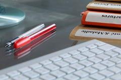 Pila de la carpeta en una mesa con el teclado Fotos de archivo