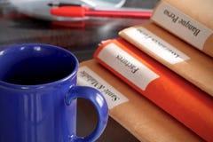 Pila de la carpeta en una mesa con una taza de café Imágenes de archivo libres de regalías