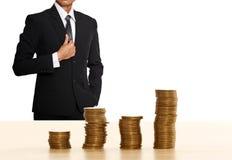 Pila de la moneda del dinero con el hombre de negocios imagen de archivo libre de regalías