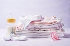 Pila de la ropa de los niños con una botella de leche y de pacificador Fotos de archivo