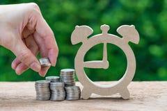 Pila de la tenencia de la mano de la mujer de dinero de las monedas que pone en la pila de moneda imágenes de archivo libres de regalías