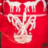Pila de la tenencia de la muchacha de bastones de caramelo de hierbabuena Día de fiesta de la Navidad Imagen de archivo