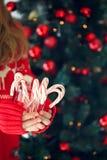 Pila de la tenencia de la muchacha de bastones de caramelo de hierbabuena Día de fiesta de la Navidad Fotos de archivo