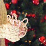 Pila de la tenencia de la muchacha de bastones de caramelo de hierbabuena Día de fiesta de la Navidad Imagenes de archivo