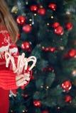 Pila de la tenencia de la muchacha de bastones de caramelo de hierbabuena Día de fiesta de la Navidad Foto de archivo libre de regalías