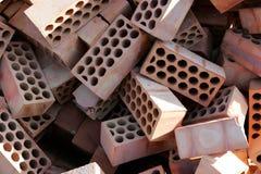 Pila de ladrillos rojos con los cirlces o los agujeros Imagen de archivo