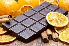 Pila de las barras de chocolate, naranjas y palillos de canela fotografía de archivo libre de regalías