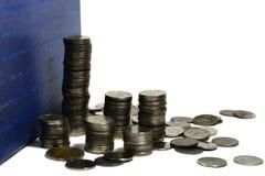 Pila de las monedas de plata con un libro en el fondo blanco Fotos de archivo