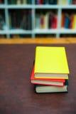 Pila de libros coloreados en la mesa de madera Imagen de archivo
