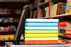 Pila de libros coloridos con el programa de lectura del e-libro Fotografía de archivo libre de regalías