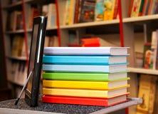 Pila de libros coloridos con el programa de lectura del e-libro Imagen de archivo