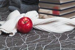 Pila de libros con el borde brillante y la manzana roja Fotos de archivo