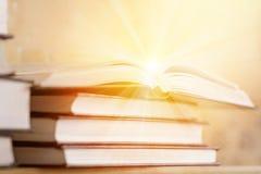 Pila de libros con el libro abierto con los rayos de la luz r Imagen de archivo libre de regalías