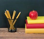 Pila de libros con la manzana y los lápices Imágenes de archivo libres de regalías