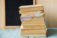 Pila de libros con la manzana y los vidrios Imagenes de archivo