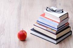 Pila de libros con la manzana y los vidrios Imagen de archivo libre de regalías