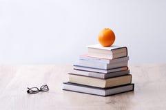 Pila de libros con la naranja en tapa Fotos de archivo libres de regalías
