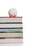 Pila de libros de textos con una batería guarra en blanco Foto de archivo libre de regalías