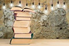 Pila de libros en el escritorio y de bombillas en el fondo fotografía de archivo libre de regalías