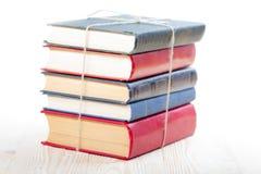 Pila de libros en la tabla de madera aislada en el fondo blanco De nuevo a escuela Copie el espacio Fotografía de archivo