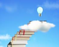Pila de libros a través de la nube con el blub y el cielo crecientes Fotos de archivo libres de regalías