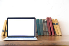 Pila de libros viejos y de ordenador portátil sobre la tabla de madera, imagen filtrada retra Foto de archivo libre de regalías