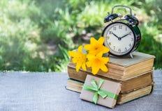 Pila de libros viejos y de un despertador Rect?ngulo y flores de regalo Tabla del verano fotografía de archivo libre de regalías