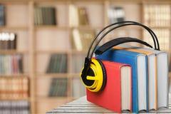 Pila de libros y de auriculares en la tabla de madera imágenes de archivo libres de regalías