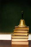 Pila de libros y de campana de escuela en el escritorio Fotos de archivo libres de regalías