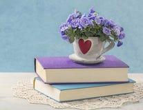Pila de libros y de flores imagenes de archivo