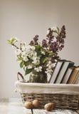Pila de libros y de flores de la primavera de una lila y de un albaricoque en una cesta Foto de archivo