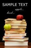 Pila de libros y de la manzana en un negro Fotografía de archivo libre de regalías