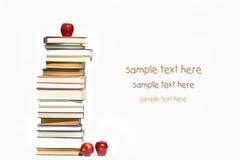 Pila de libros y de manzanas en blanco Fotos de archivo libres de regalías