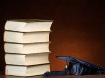 Pila de libros y del casquillo de la graduación Foto de archivo libre de regalías