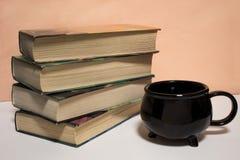 Pila de libros y de una taza en el fondo blanco imagen de archivo libre de regalías