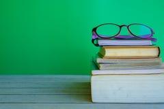 Pila de libros y de vidrios del ojo en el top en la tabla de madera imágenes de archivo libres de regalías