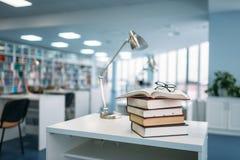 Pila de libros y de vidrios en la tabla en biblioteca imagen de archivo libre de regalías