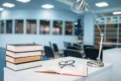 Pila de libros y de vidrios en la tabla en biblioteca imagen de archivo