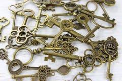 Pila de llaves de cobre amarillo antiguas en un fondo de madera apenado Imagen de archivo libre de regalías